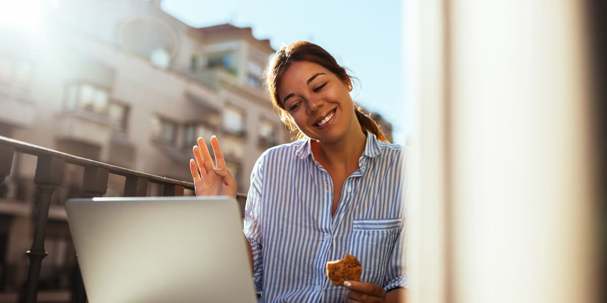 cheerful-young-woman-staying-connected-via-laptop