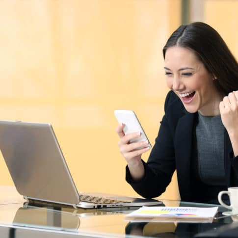 excited businesswoman after closing a virtual sales call on her cell phone