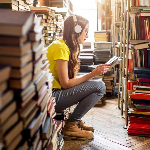 young woman wearing headphones surrounded by a heap of books in the library