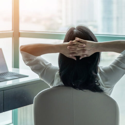 Asian business woman relaxing at her desk with arms behind head
